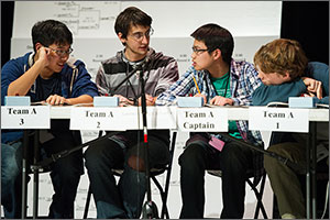 Four teenage boys sit behind a table during the 2013 Colorado High School Science Bowl, discussing the answer to a question in the final round of the competition.