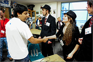 A member of one high school team shakes hands with a member of an opposing team. Several other student participants look on.