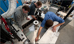 In this photo, three NREL employees work on a battery calorimeter.