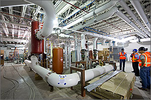 Photo of a large mechanical room and men in hard hats.