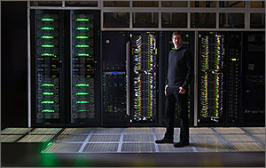Photo of a man standing in front of computer racks that are part of NREL's high performance computing data center.