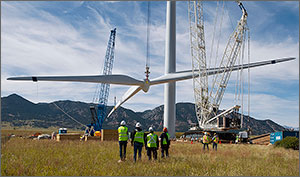 In this photo, a crane lifts a rotor and blade assembly off the ground to attach to a Gamesa wind turbine. Four workers stand in the foreground with their backs facing the camera as they watch the item being lifted. Two other workers stand closer to the turbine to the right of those four workers. The tower of the turbine is visible in the center of the shot, and a smaller craneis assisting the lift to the left of the tower. Mountains are visible in the background.