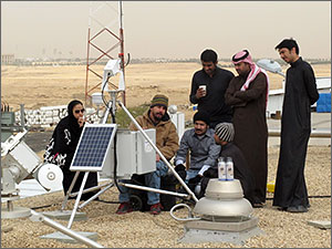 Photo of a group people standing in the desert installing a solar monitoring instrument.