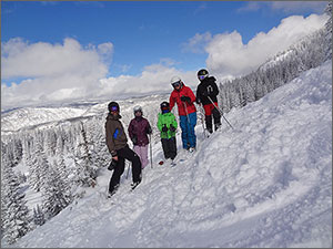 Photo of a family on a mountain side in ski gear.