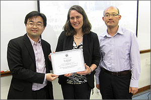 Photo of a woman holding a certificate. Two men stand on either side of the woman.