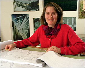 Photo of a woman sitting at a desk with photos of buildings in the background.