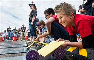 In this photo, a boy grins widely as he holds a yellow folder over his model solar car. In the background are several black neoprene tracks and other middle-school students awaiting the starting signal. An adult race judge holds her hand in the air, signaling that everything is ready for the start of the race.