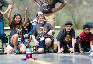 In this photo, four middle schoolers are crouched at the edge of a race track. A girl on the left holds up both hands signaling victory, while the boy next to her smiles. To the right are two boys whose faces register concern as they watch their car move down the track.