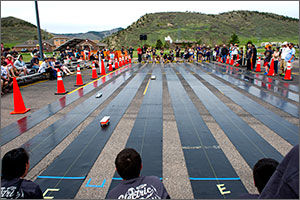 In this photo, four cars can be seen on the neoprene tracks, bordered by orange construction cones. In the background are several middle-school students and behind them, the foothills.