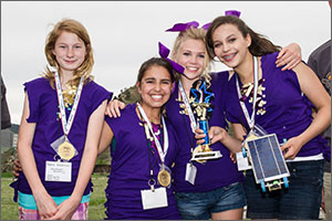 In this photo, four girls in purple tops and purple hair ribbons smile at the camera. The one on the right holds a trophy and the solar-powered model car. All four girls are wearing medals around their necks.