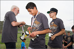 In this photo, a man in a white beard and glasses presents a trophy to a middle-school boy who is holding a car made of a sheet of balsa wood. A second boy awaits his turn to get a medal. All three are wearing the official electric car competitions grey T-shirt.