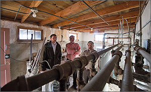 Photo of three men standing in the basement of a home.