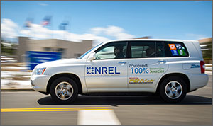 A hydrogen fuel cell powered Toyota sport utility vehicle emblazoned with an NREL logo drives past a building on the NREL campus.
