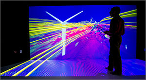 In this photo, a man in silhouette holding a remote-control device stands in front of a giant screen looking at ribbons of yellow flowing past a wind turbine while purples, whites, and blues enhance the three-dimensional effect.