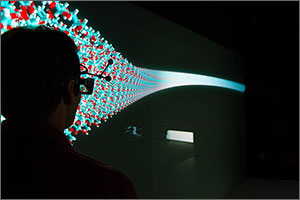 In this photo, a silhouette of a man's upper body is in the foreground. The man is wearing special glasses. In the background is a model of a molecule in the shape of a cornucopia, colored mostly blue and red.
