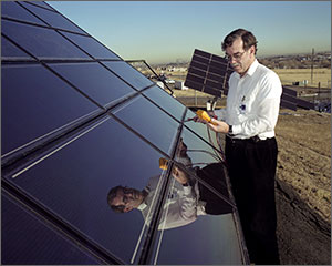 In this photo, a scientist in a white shirt reads numbers off a yellow monitor he is holding in his hand. To the left is a large solar panel, with other panels in the background.