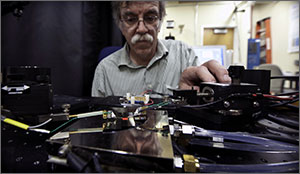 In this photo a scientist loads photovoltaic cells into measurement equipment in a laboratory.
