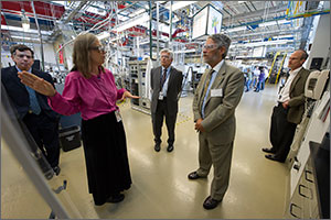 In this photo, a woman in a lavender blouse uses her hands to make a point to two men in business suits. In the background are the pipes, hoses, machinery, and scaffolding of a busy laboratory.