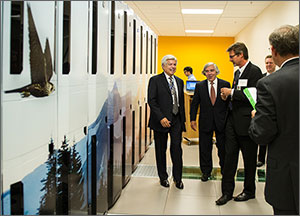 In this photo, three men share a laugh as they stand in front of a high-performance computer (HPC) that takes up the entire area to their right. The HPC has a mural of trees, mountains, and a bird of prey.
