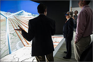 In this photo, a man wearing high-tech glasses gazes at a huge screen displaying a wind turbine. Ribbons of orange represent the way wind flows downstream when the blades hit it. A man with his back to the camera explains the process, while two others look on.