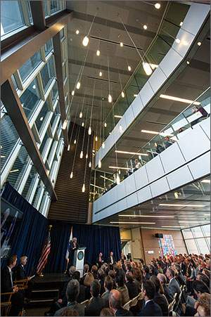 This photo shows a seated crowd watching a man in a suit at a raised podium. The upper two-thirds of the photo shows windows, hanging pendant lights, and breezeways.