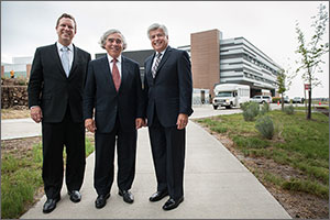 In this photo, three men in dark suits stand on a sidewalk smiling. Behind them is a three-story laboratory building, with a shuttle bus parked outside.