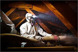 Photo of a man in a suit blowing insulation into an attic.