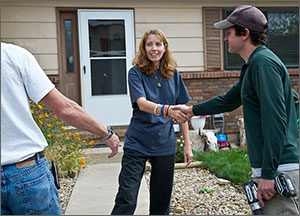 Photo of a woman shaking hands with a weatherization professional.