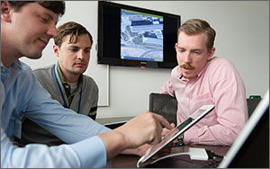 In this photo, three men sit around an electronic tablet while a screen in the background projects a larger image of what they see on the tablet, an aerial view of a commercial building.