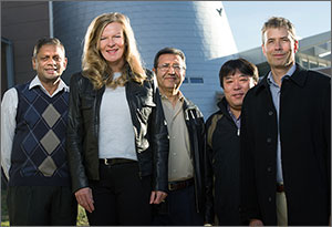 This photo is a group shot of five scientists standing outside a lab building.