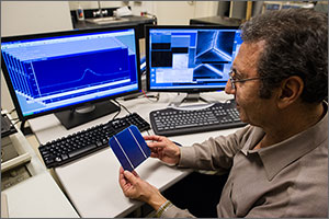 In this photo, a researcher in glasses holds a solar wafer about the size of a CD case. In the background are two computer screens displaying graphs of the performance of similar wafers.