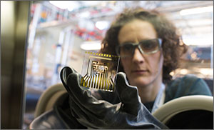 In this photo, a scientist wearing safety glasses inspects a test card that she is holding inside an inert atmosphere chamber. The test card is a square and transparent glass piece on which gold and calcium are deposited, giving the appearance of ribbons of yellow and silver forming a maze-like pattern.