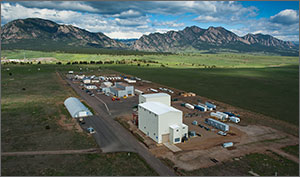 An aerial photograph of the testing facility with many buildings in the foreground and mountains in the background. The dynamometer test facility is a tall white building centered in the foreground.