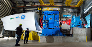 Two men stand in front of the test equipment in the dynamometer facility discussing work being done. Behind them are two large blue machines that make up the dynamometer test apparatus. A white wind turbine nacelle system is attached to these devices to their left.