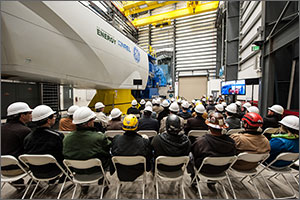 A group of people wearing hard hats sit in chairs and listen to a speaker on stage. Behind the speaker is a dynamometer test system. To the speaker's right is a large white wind turbine nacelle that is connected to the dynamometer system. Three other speakers sit in chairs just off the stage. To their left, a video screen shows the testing system in operation.