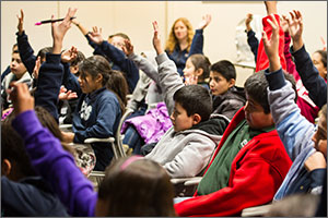 A group of students raise their hands to answer a question while participating in a classroom education session at NREL's Education Center.