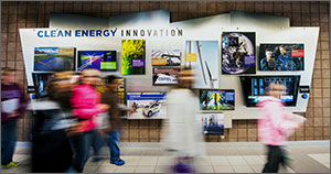 "Six students are out of focus in the foreground of this photo as they walk past a ""Clean Energy Innovation"" display in the background. The display features numerous photographs of clean energy technologies."