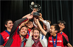 Photo of a team of high school students holding a trophy high over their coach's head.