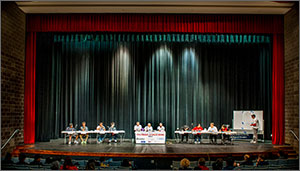 Photo of a stage in an auditorium; onstage are two teams sitting at tables to compete.