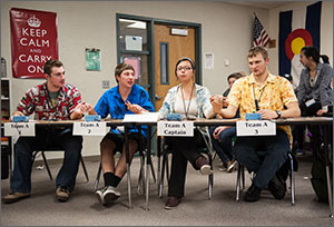 Photo of four high school students sitting at desks and holding hands and concentrating.