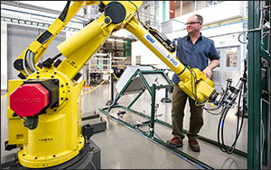 In this photo, a man stands behind a large yellow robot with his hands on the robot's arm.