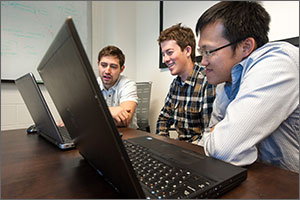 Photo of three young men looking at two laptops.