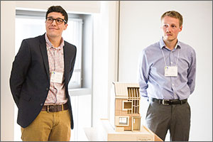 Photo of two men standing with a small-scale model home.