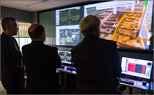 Photo of three people looking at computer screens in a control room.
