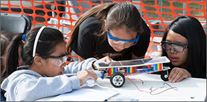 Photo of a team of girls carefully examining their solar model racecar.