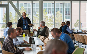 People sit at rows of tables having lunch inside the NREL Café. In the rear of the photo one man stands while holding a plate of food, speaking to two seated men. Behind him is a wall of windows that allow those inside the building to see the building adjacent.