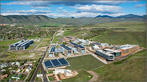 An aerial photo of the NREL campus shows the buildings on the campus with the mountains in the background.