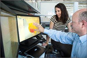 Photo of two scientists looking at two computer screens, one of which has a map of the United States.