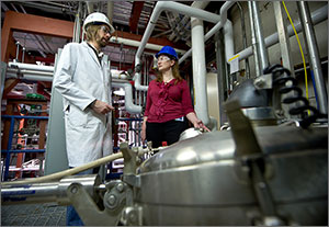 Photo of a man and woman in hard hats inside NREL's Integrated Biorefinery Research Facility.
