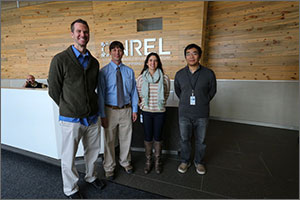 Four smiling people—three men and a woman—stand in front of a wooden wall in an office.